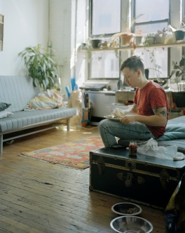 Jamie Weiss, a filmmaker originally from Carroll Gardens in Brooklyn, has lunch in the living room of his flat. He likes this particular area of the apartment because of the amount of light coming in from the tall windows. April 2013.